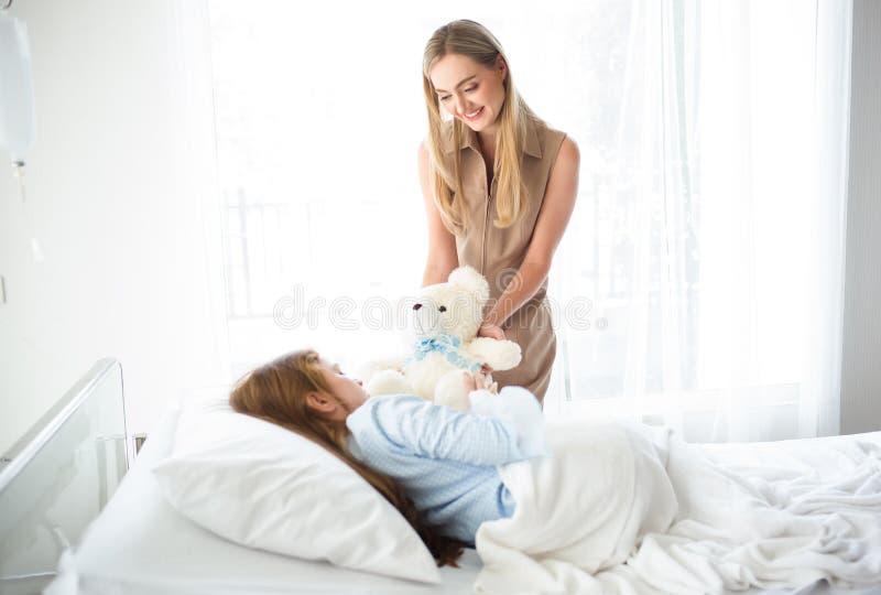 有玩具熊参观的女儿的微笑的母亲在医院 免版税库存图片