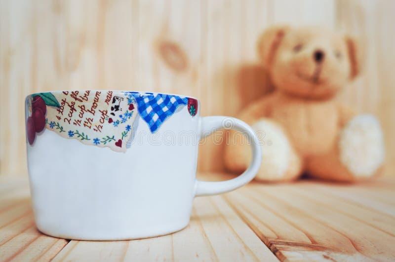 有玩具熊和木背景的一个咖啡杯 例证百合红色样式葡萄酒 免版税库存照片