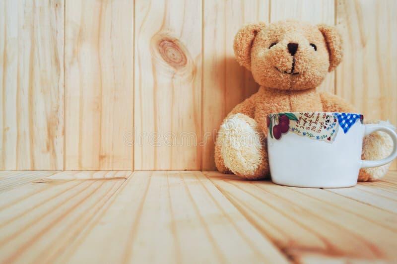 有玩具熊和木背景的一个咖啡杯 例证百合红色样式葡萄酒 库存图片