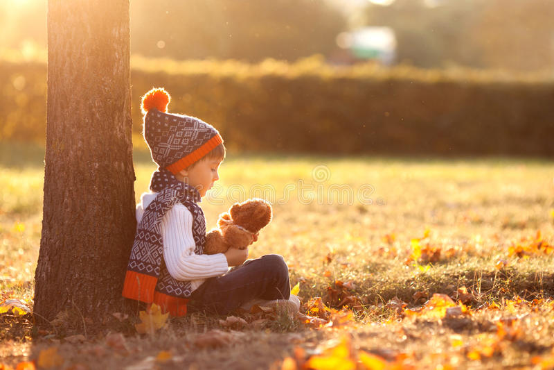 有玩具熊的可爱的小男孩在公园在秋天天 免版税库存图片
