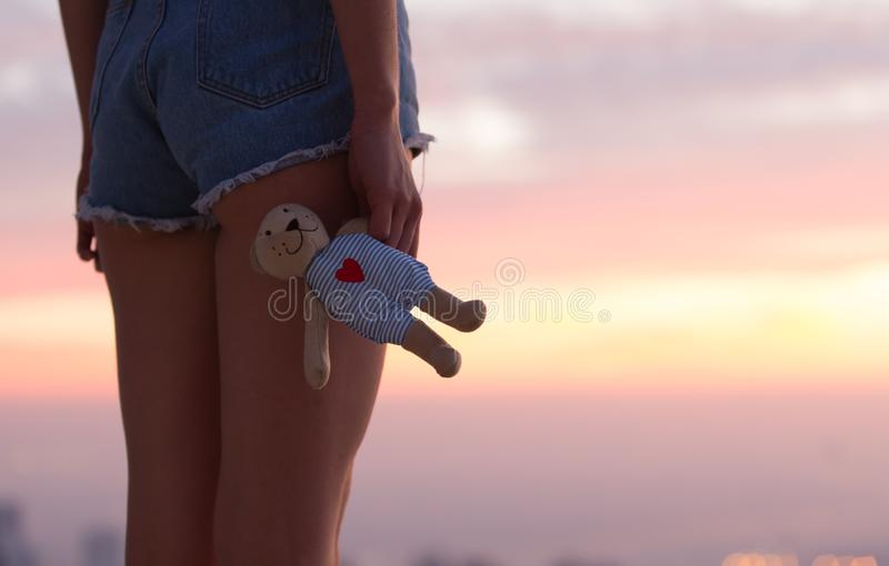 有玩具熊的哀伤的孤独的女孩在日落 库存照片