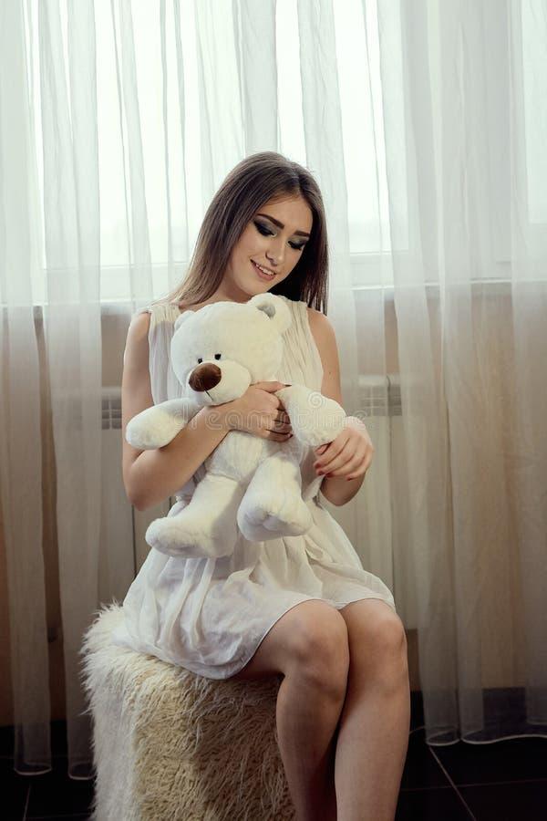 有玩具熊的女孩生活方式设计的 年轻白种人模型 美丽的表面妇女 免版税库存图片