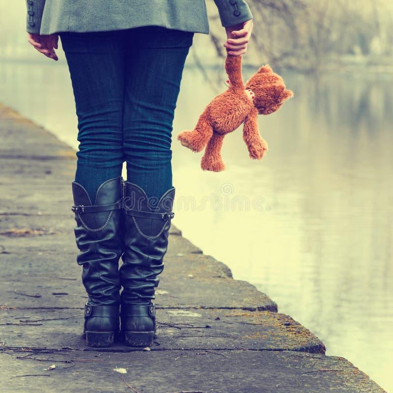 有玩具熊的孤独的女孩在河附近 免版税图库摄影