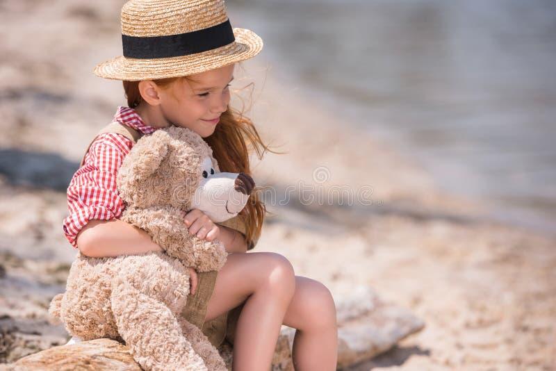 有玩具熊的孩子在海滨 库存图片