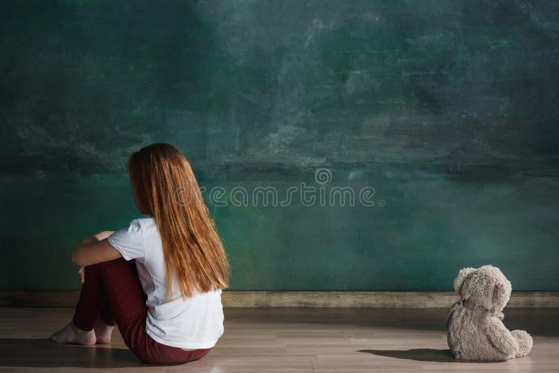 有玩具熊的小女孩坐地板在空的屋子里 孤独性概念 图库摄影