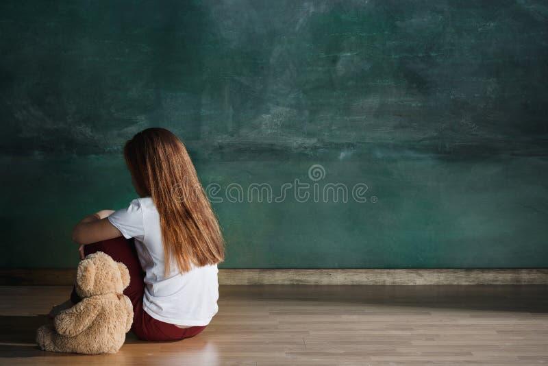 有玩具熊的小女孩坐地板在空的屋子里 孤独性概念 免版税库存图片