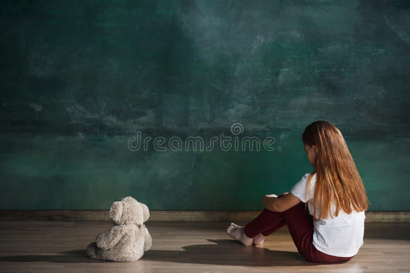 有玩具熊的小女孩坐地板在空的屋子里 孤独性概念 库存照片