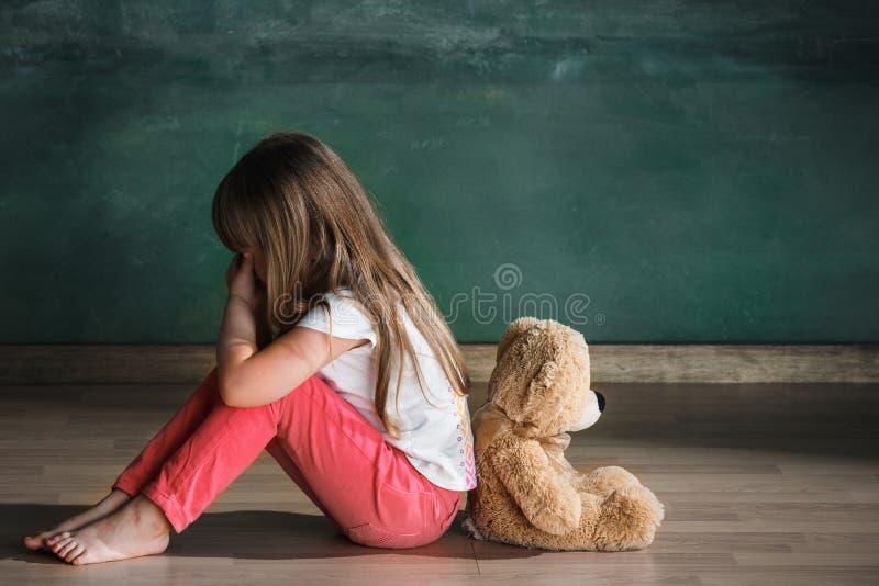 有玩具熊的小女孩坐地板在空的屋子里 孤独性概念 免版税图库摄影