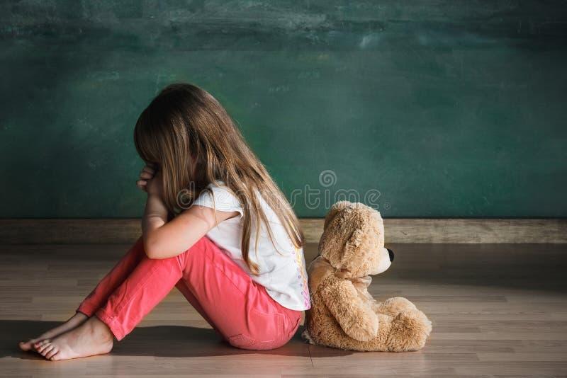有玩具熊的小女孩坐地板在空的屋子里 孤独性概念 免版税库存照片