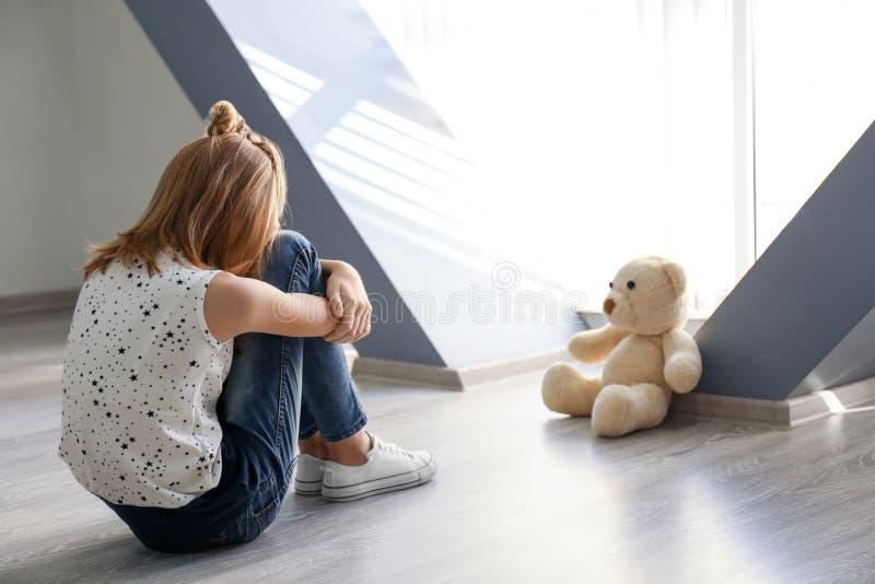 有玩具熊的小女孩坐地板在窗口附近 免版税图库摄影