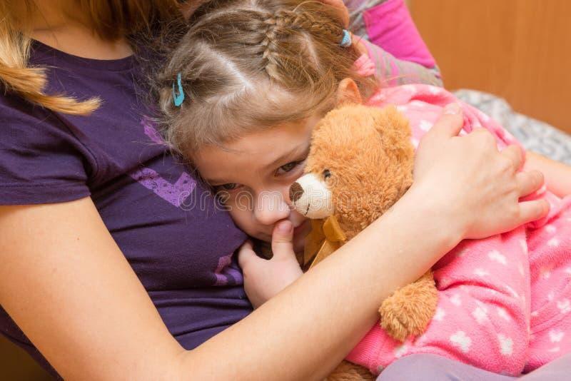 有玩具熊的小女孩紧贴了给她的有一个哀伤的表示的母亲在他的面孔 免版税库存图片