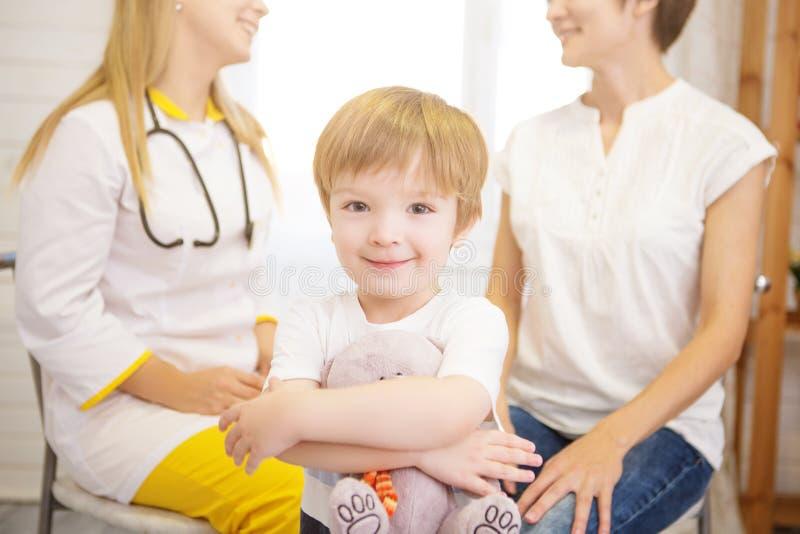 有玩具熊的小男孩看照相机 女性医生和母亲背景的 库存照片