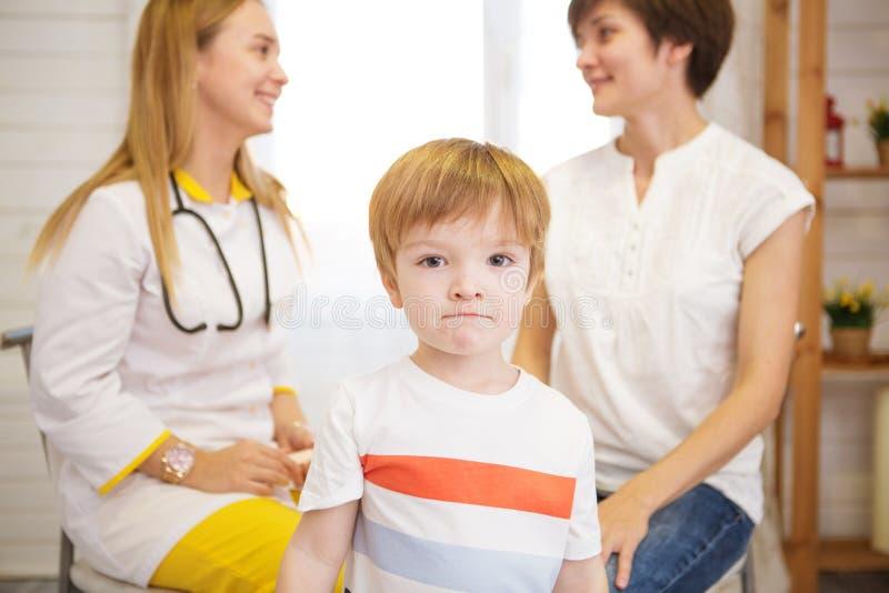 有玩具熊的小男孩看照相机 女性医生和母亲背景的 免版税图库摄影