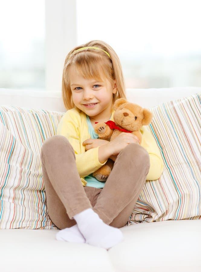 有玩具熊的微笑的女孩坐沙发 免版税图库摄影