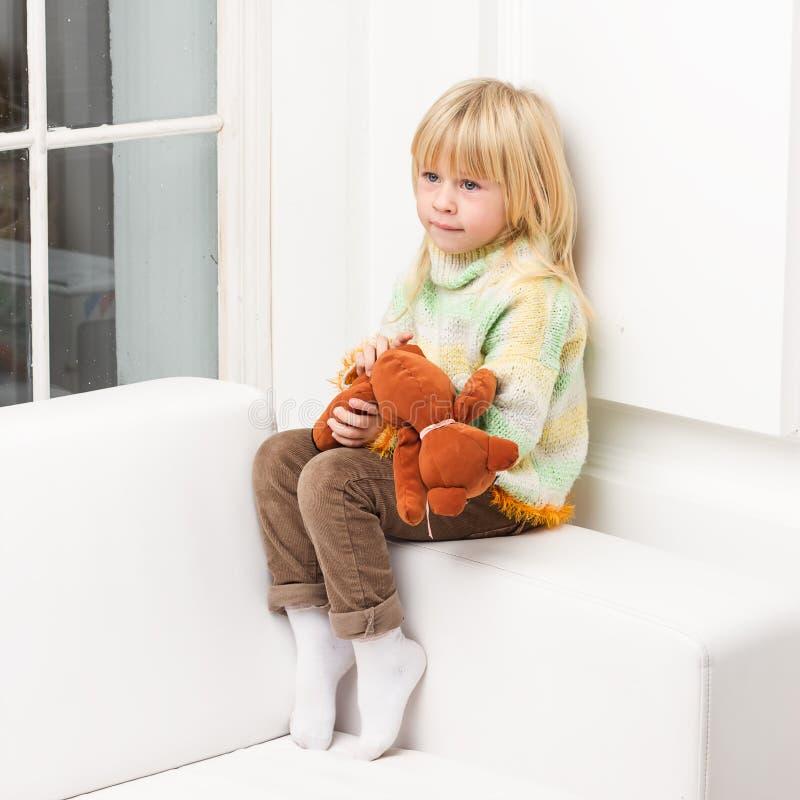 有玩具熊的微笑的小女孩坐沙发家 库存图片