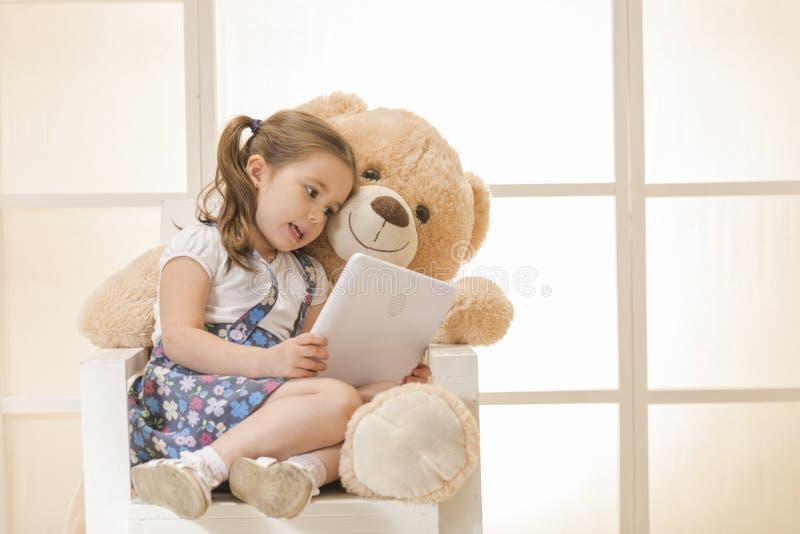 有玩具熊的愉快的小女孩 图库摄影