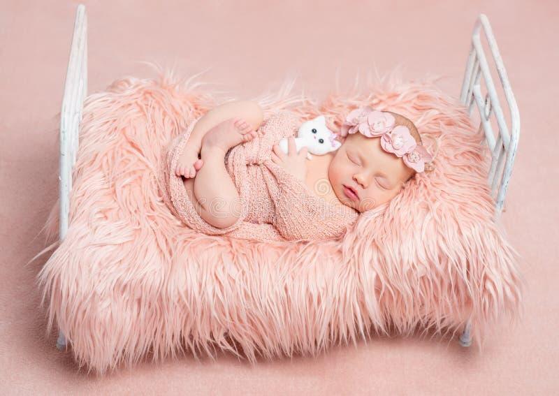有玩具猫的逗人喜爱的睡觉的新出生的女孩在一点床上 免版税库存照片