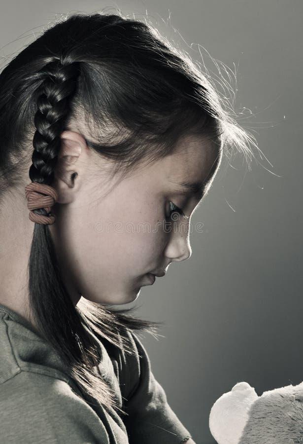 有玩具的哀伤的小女孩在灰色背景 库存图片