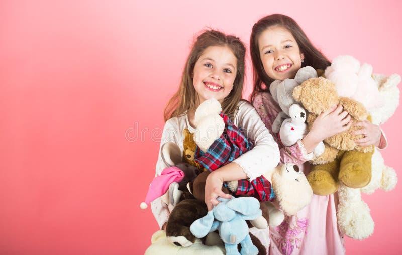 有玩具的小女孩 站立和接受plushs的两个美丽的愉快的女孩在儿童居室戏弄 柔软和 免版税图库摄影