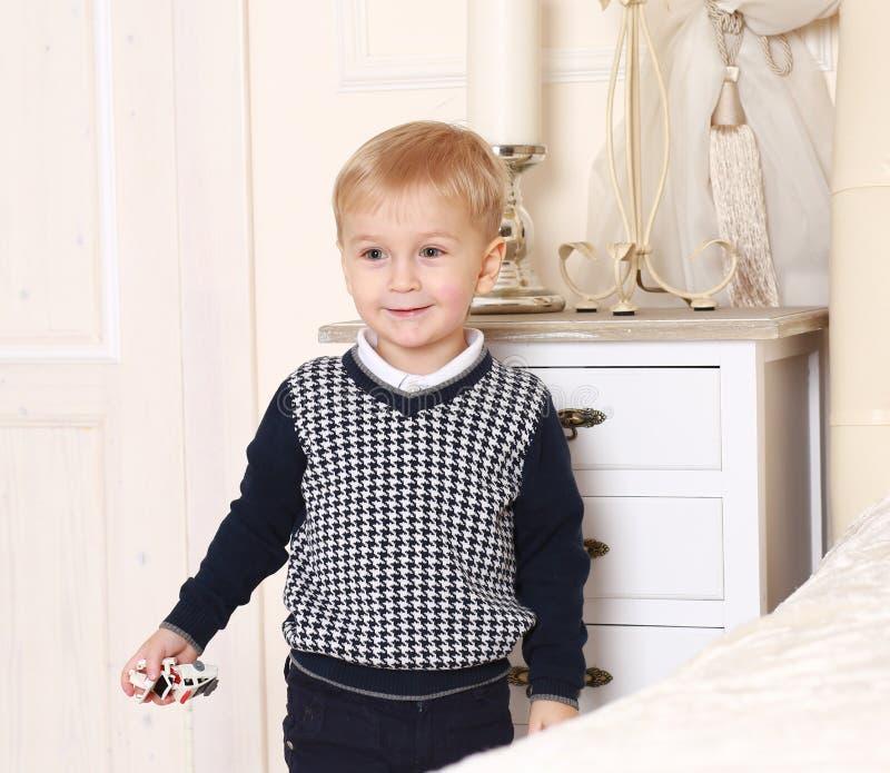 有玩具的小男孩在手中 免版税库存图片