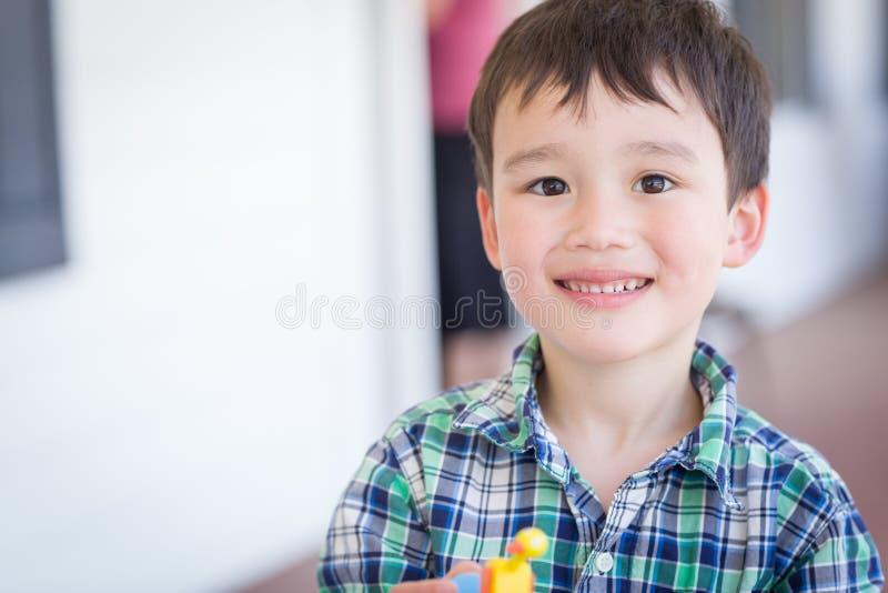 有玩具的混合的族种中国和白种人年轻男孩画象  库存图片
