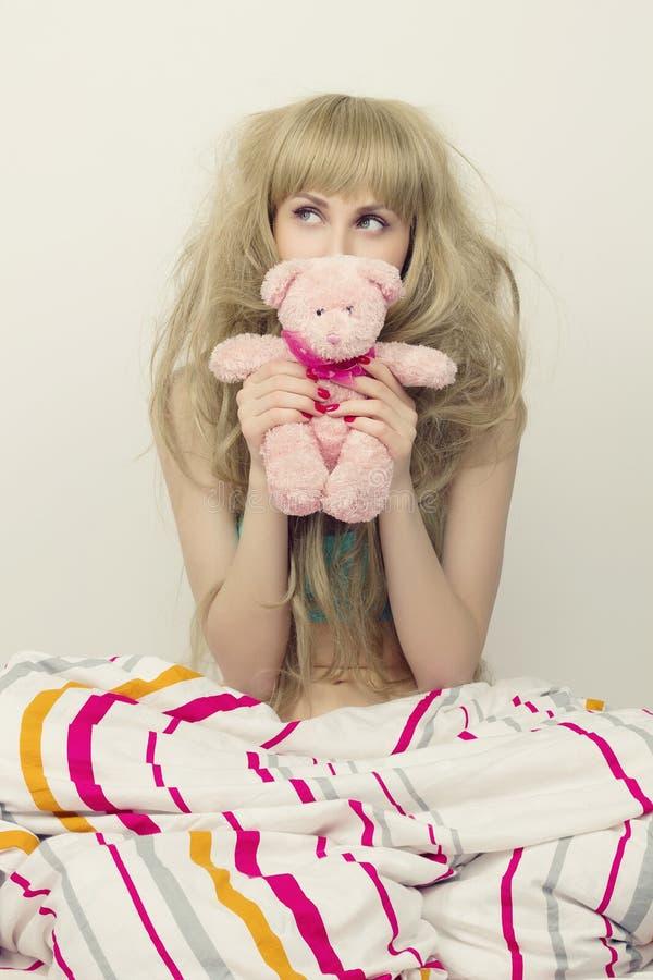 有玩具的美丽的女孩在床上 免版税库存照片
