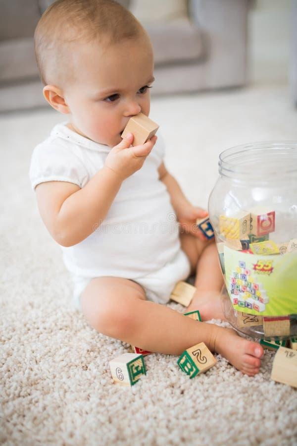 有玩具的逗人喜爱的矮小的婴孩坐地毯 图库摄影