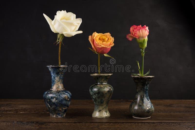 有玫瑰的三个小大理石花瓶在黑色 库存图片