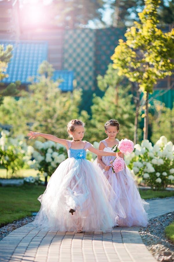 有玫瑰美丽的花束的两个可爱的女孩在手上去婚礼 库存照片