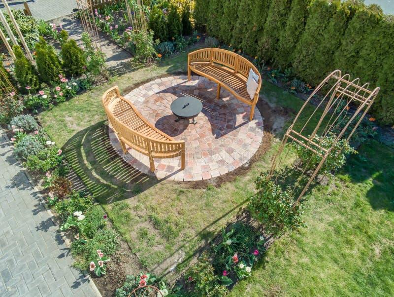 有玫瑰色曲拱、壁炉和舒适长木凳的美妙地装饰的和被种植的庭院 库存照片
