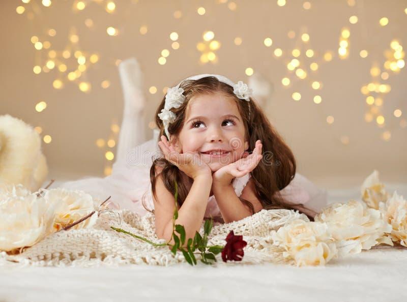 有玫瑰色花的女孩孩子在圣诞灯,黄色背景,桃红色礼服摆在 库存照片