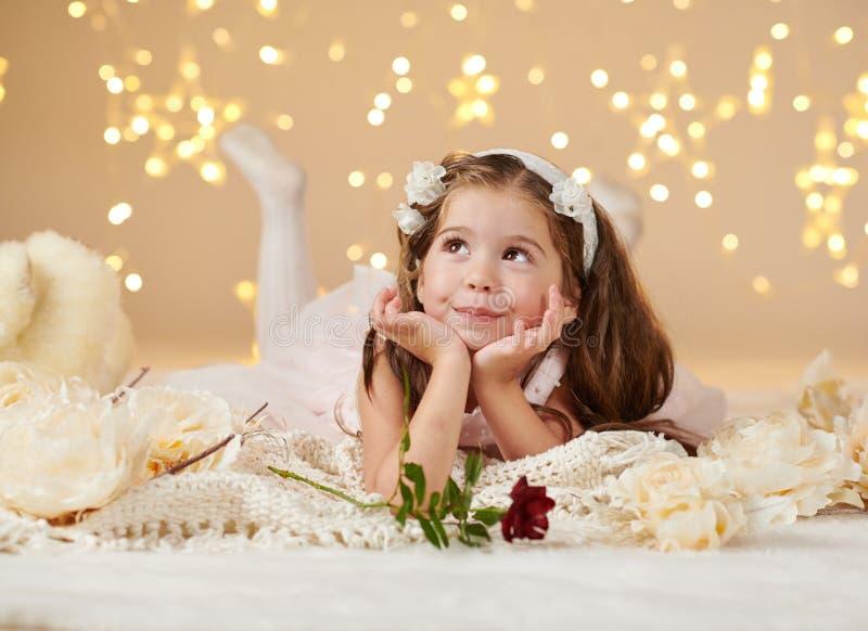 有玫瑰色花的女孩孩子在圣诞灯,黄色背景,桃红色礼服摆在 免版税库存照片
