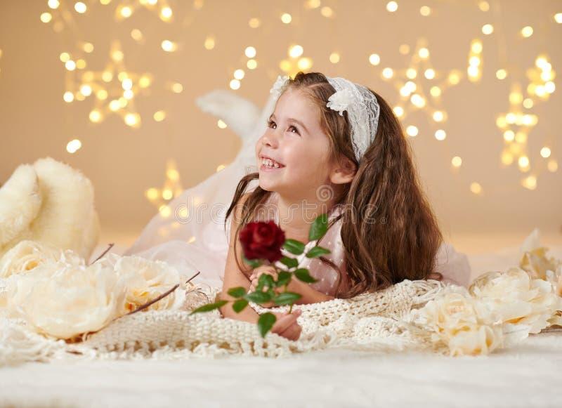 有玫瑰色花的女孩孩子在圣诞灯,黄色背景,桃红色礼服摆在 图库摄影