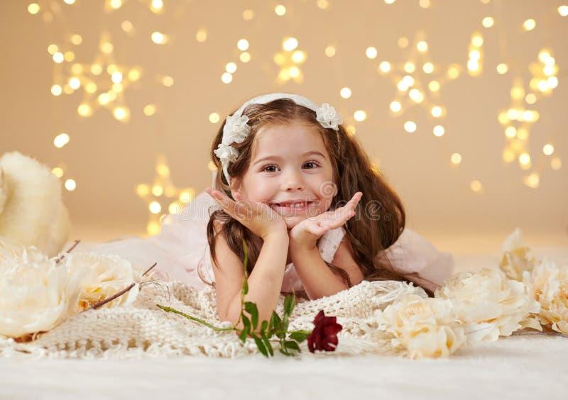 有玫瑰色花的女孩孩子在圣诞灯,黄色背景,桃红色礼服摆在 库存图片