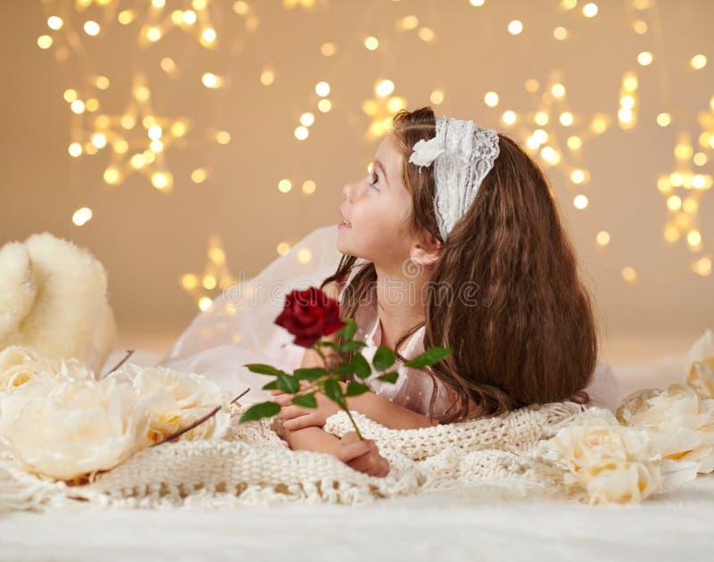 有玫瑰色花的女孩孩子在圣诞灯,黄色背景,桃红色礼服摆在 免版税库存图片
