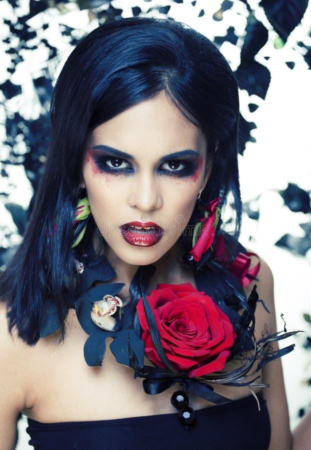 有玫瑰色首饰的俏丽的深色的妇女,黑和红色,明亮组成kike一个吸血鬼特写镜头红色嘴唇 免版税库存照片