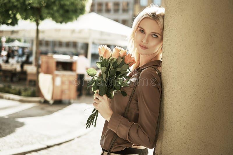 有玫瑰花束的可爱的妇女  免版税库存照片