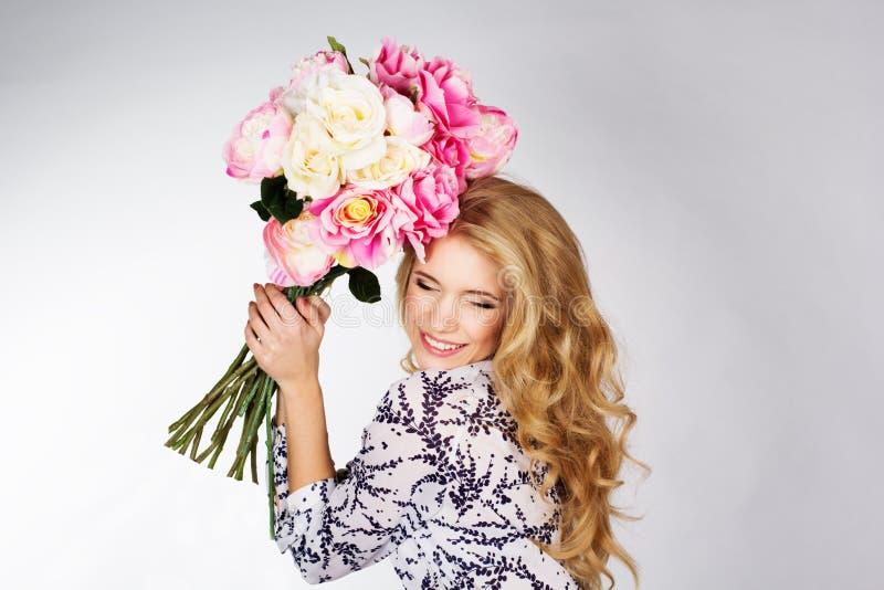 有玫瑰花束的愉快的微笑的白肤金发的女孩  免版税库存图片
