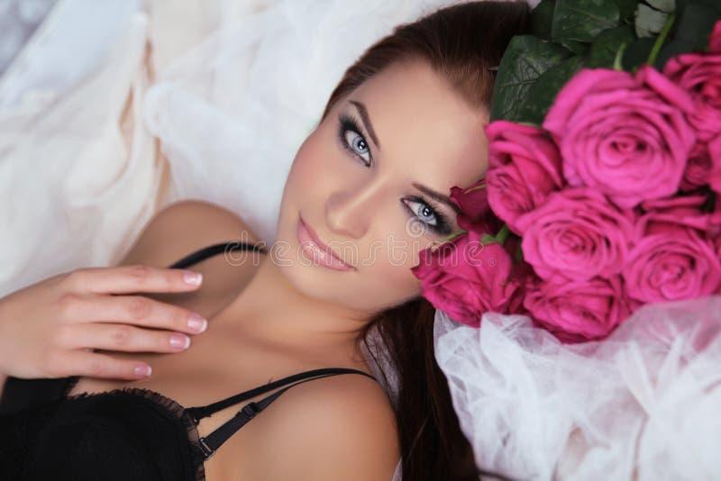 有玫瑰花的美丽的女孩。秀丽式样妇女面孔。穿孔机 图库摄影