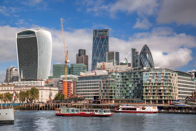有现代城市建筑学的伦敦反对有小船的河在英国,英国 图库摄影