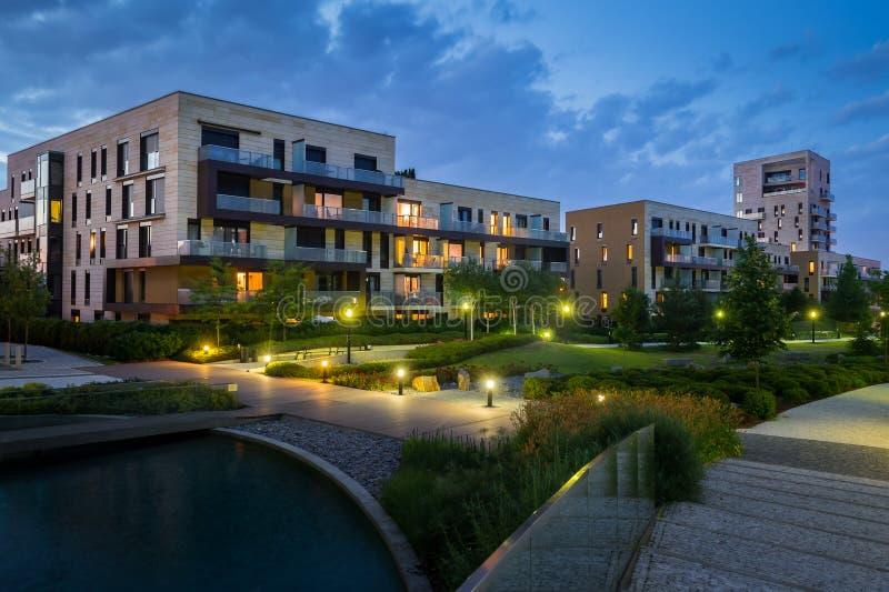 有现代房子的绿色公园在背景中在晚上 免版税库存照片