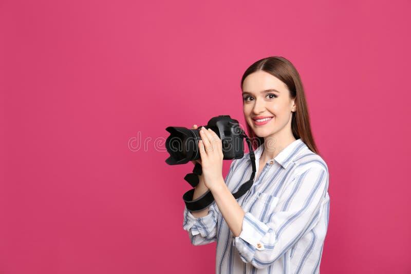 有现代照相机的专业摄影师在桃红色 免版税库存照片