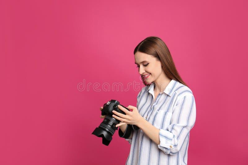 有现代照相机的专业摄影师在桃红色 免版税图库摄影