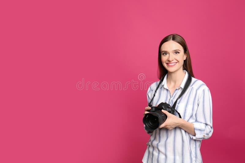 有现代照相机的专业摄影师在桃红色 r 免版税库存图片