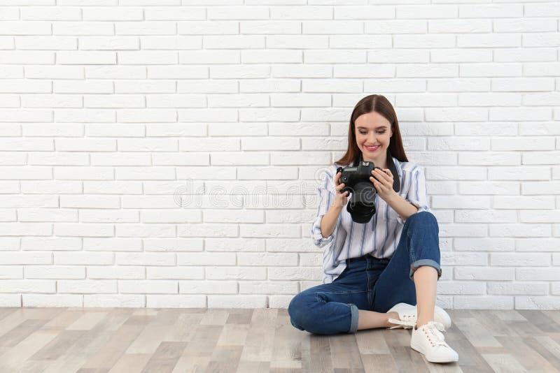 有现代照相机的专业摄影师在白色砖墙附近 免版税库存图片