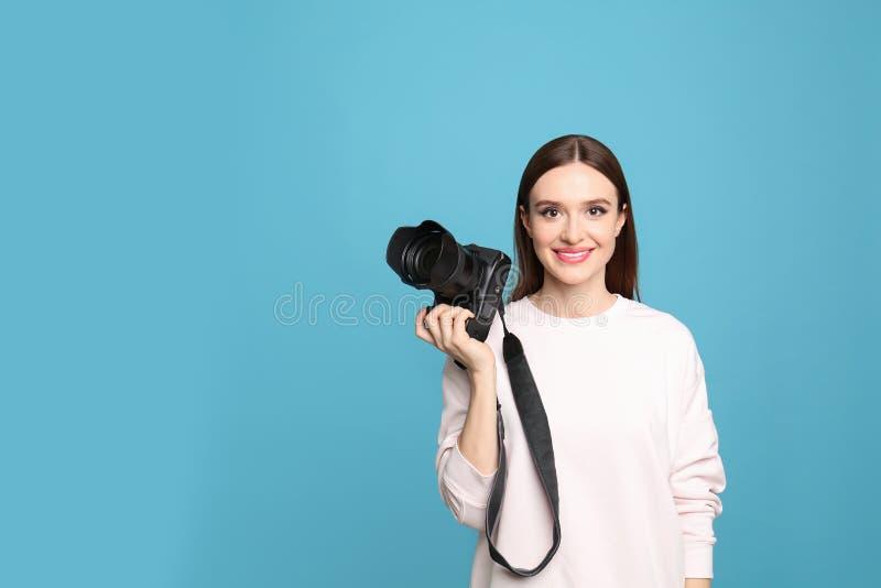 有现代照相机的专业摄影师在蓝色背景 免版税库存图片