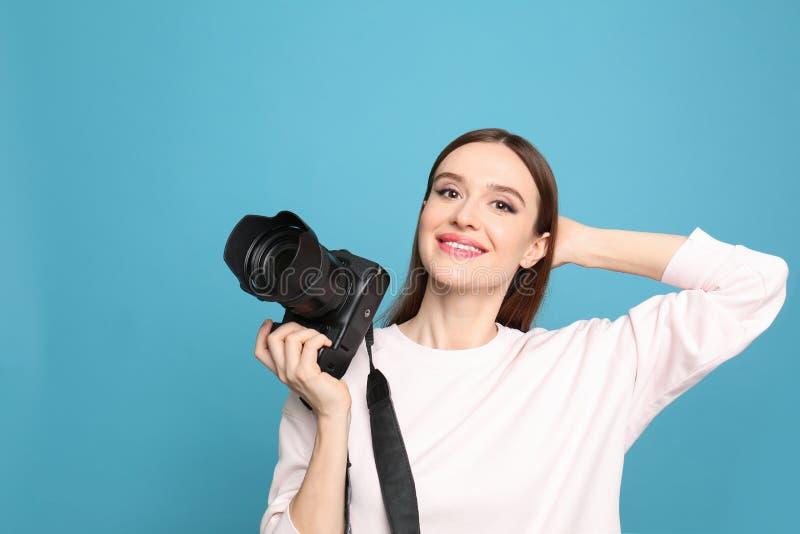 有现代照相机的专业摄影师在蓝色背景 库存图片