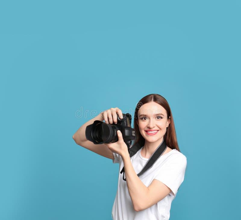 有现代照相机的专业摄影师在蓝色背景 图库摄影