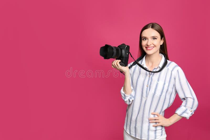 有现代的专业摄影师在桃红色背景 r 免版税库存图片