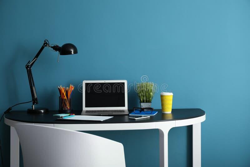 有现代膝上型计算机的时髦的工作场所在颜色墙壁附近 免版税库存图片